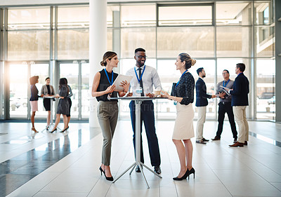 Buy stock photo Shot of a group of businesspeople having a meeting at a conference