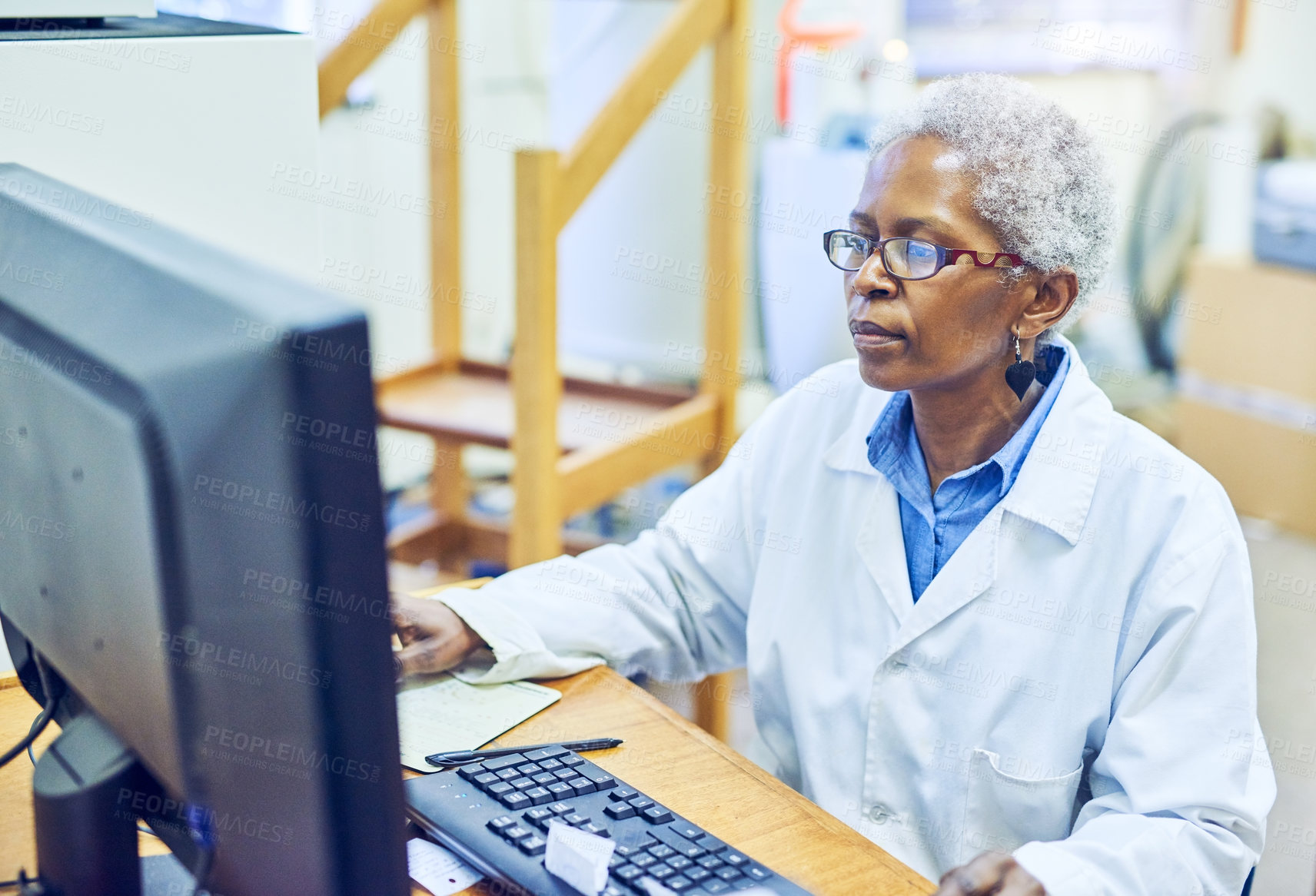 Buy stock photo Shot of a mature scientist working on a computer in a lab