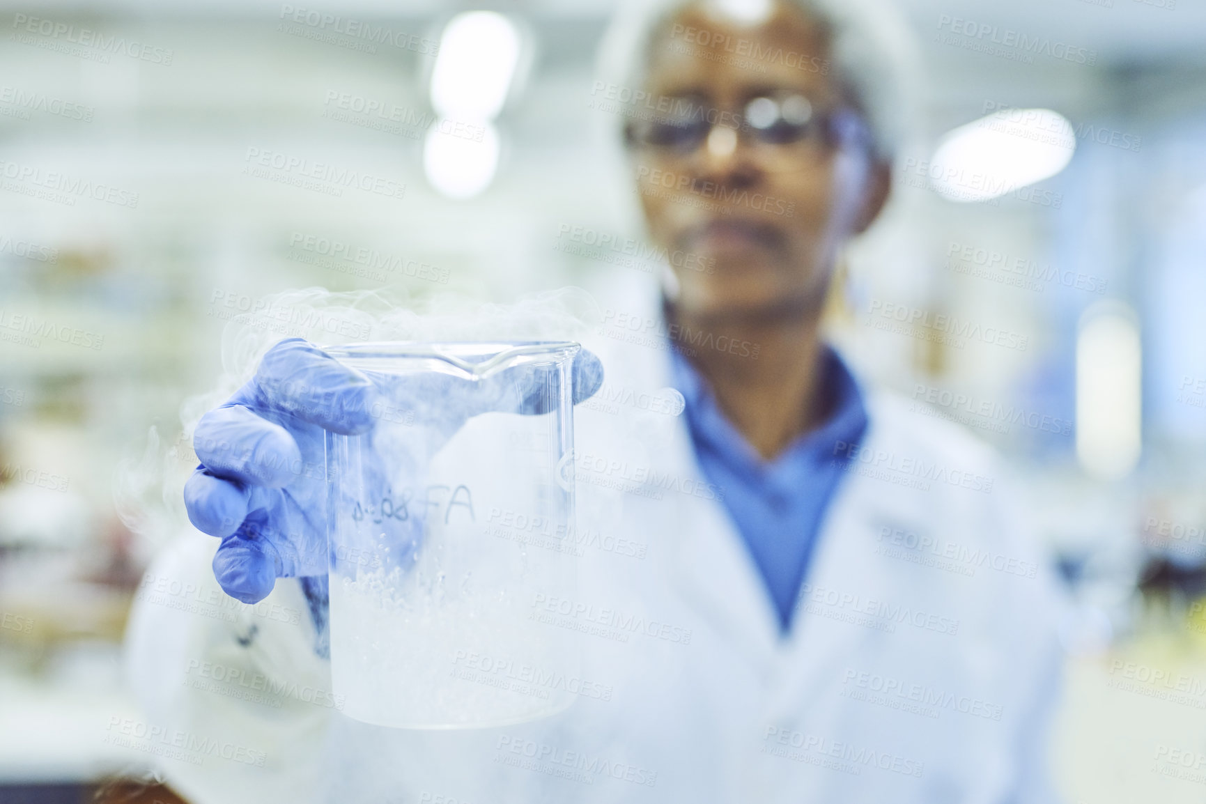 Buy stock photo Shot of a mature scientist holding a beaker in a lab