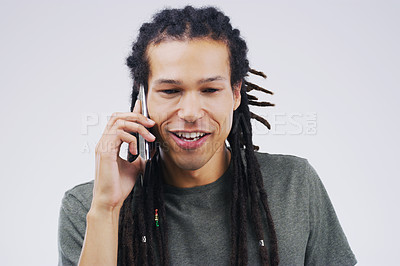 Buy stock photo Studio shot of a young man using a mobile phone against a grey background