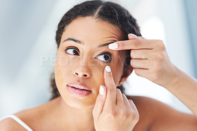 Buy stock photo Cropped shot of an attractive young woman going through her morning beauty routine in the bathroom