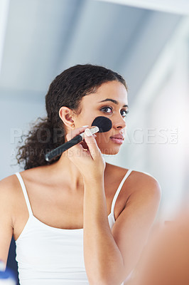 Buy stock photo Cropped shot of a young woman applying makeup to her cheeks in the bathroom at home