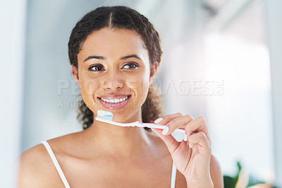 Buy stock photo Cropped shot of an attractive young woman brushing her teeth in the bathroom at home