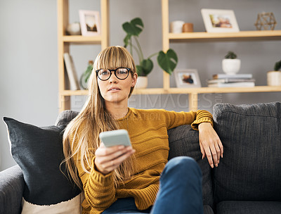Buy stock photo Shot of a young woman watching television on the sofa at home