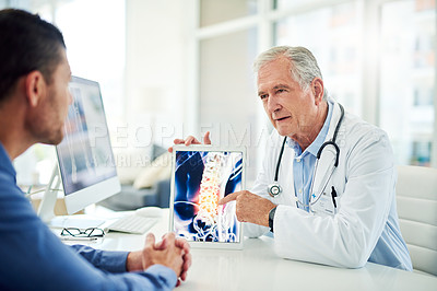 Buy stock photo Cropped shot of a confident elderly doctor shoeing test results to a patient inside of his office during the day