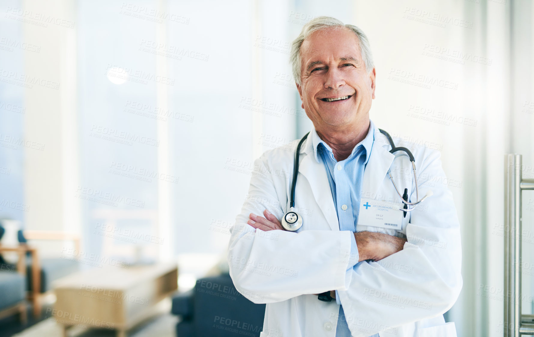 Buy stock photo Portrait of a confident elderly doctor standing with arms folded inside of his office during the day