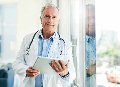 Buy stock photo Portrait of a confident elderly doctor browsing on a digital tablet while standing inside of his office