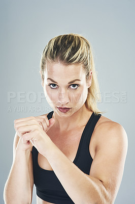 Buy stock photo Studio portrait of a sporty young woman punching against a grey background