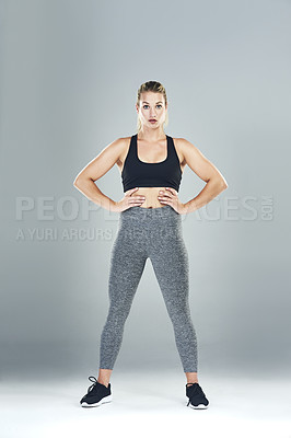 Buy stock photo Studio portrait of a sporty young woman standing against a grey background