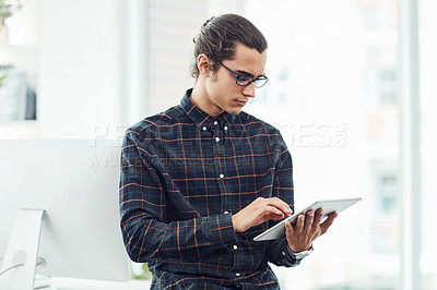 Buy stock photo Shot of a young designer working on a digital tablet in an office