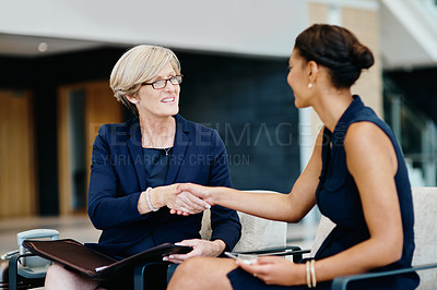 Buy stock photo Shot of two businesspeople having a discussion together and shaking hands while being seated inside of a office building