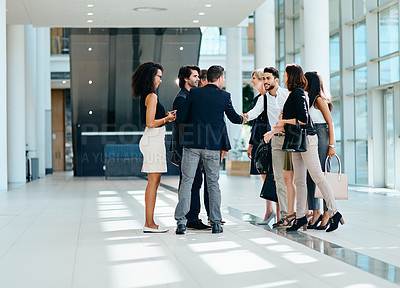 Buy stock photo Shot of a group of businesspeople greeting each other inside of a office at work