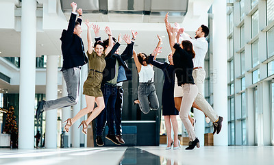 Buy stock photo Shot of a group of cheerful businesspeople jumping in the air for joy inside of the office building
