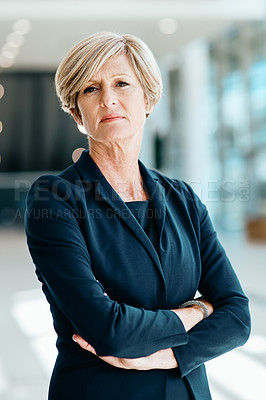 Buy stock photo Shot of a confident mature businesswoman standing with her arms folded inside of the office at work