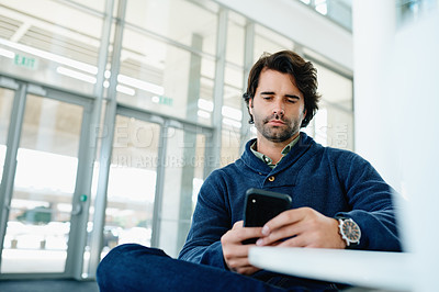 Buy stock photo Shot of a carefree young businessman texting on his cellphone while bing seated in a chair at work