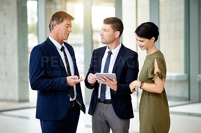 Buy stock photo Shot of a group of businesspeople using a digital tablet together in an office