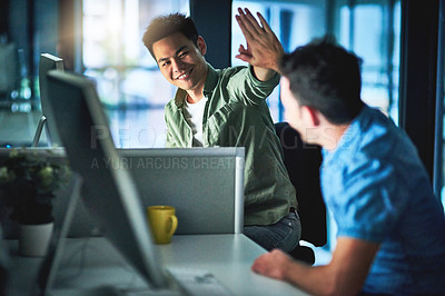 Buy stock photo Cropped shot of two young male designers high fiving while working late at night in their office