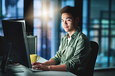 Buy stock photo Cropped portrait of a handsome young male designer working late at night on a computer in the office