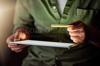 Buy stock photo Cropped shot of an unrecognizable businessman using his tablet to shop online while working late at night in the office