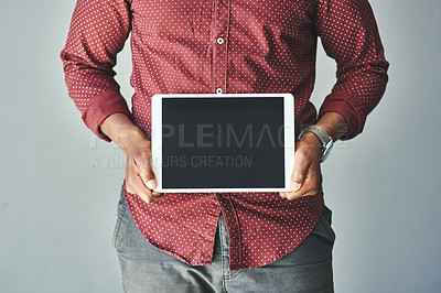 Buy stock photo Cropped shot of an unrecognizable man holding a digital tablet against a grey background