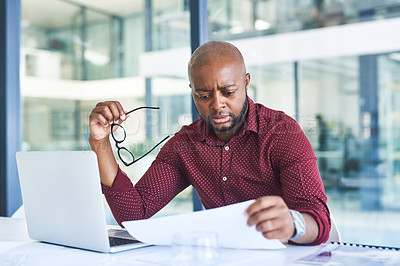 Buy stock photo Cropped shot of a young designer working on paperwork while sitting at his desk