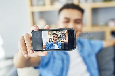 Buy stock photo Shot of a cheerful young man taking a self portrait with his cellphone while relaxing at home