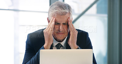 Buy stock photo Shot of a mature businessman looking stressed out while working in an office