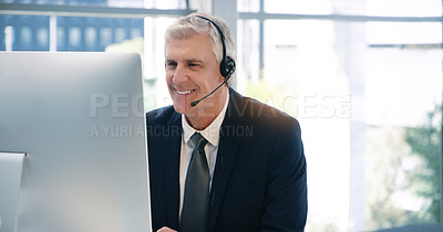 Buy stock photo Shot of a mature businessman wearing headphones while working on a computer in an office