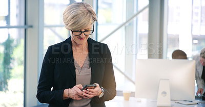 Buy stock photo Shot of a mature businesswoman texting on a cellphone in an office