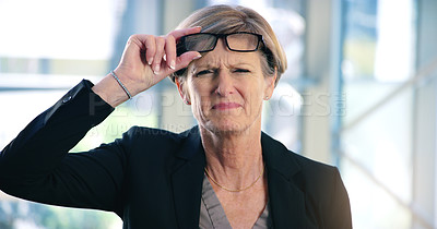 Buy stock photo Portrait of a mature businesswoman frowning while holding a pair of spectacles in an office