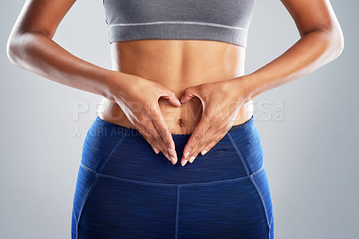 Buy stock photo Cropped studio shot of an unrecognizable young woman making a heart shape on her stomach