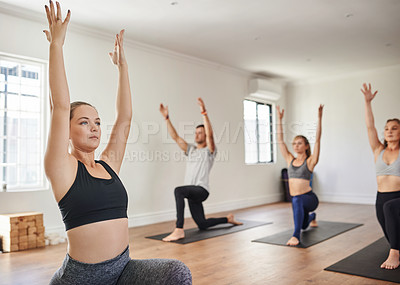 Buy stock photo Shot of a group of focused young people doing yoga poses during a session inside of a studio