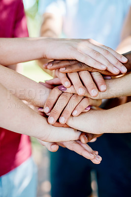 Buy stock photo Cropped shot of a group of teenagers joining their hands in solidarity outdoors