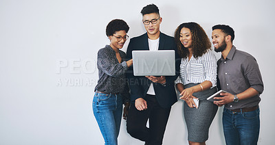 Buy stock photo Studio shot of a group of businesspeople using a laptop together against a white background