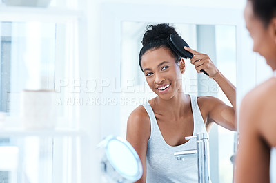 Buy stock photo Cropped shot of a beautiful young woman brushing her hair in the bathroom at home
