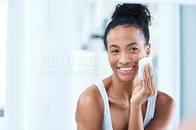 Buy stock photo Portrait of an attractive young woman cleaning her face with a cotton pad in the bathroom at home
