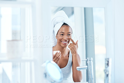 Buy stock photo Shot of a beautiful young woman applying moisturizer to her face