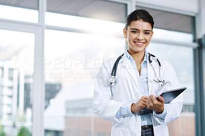 Buy stock photo Portrait of a young female doctor using a digital tablet in a hospital