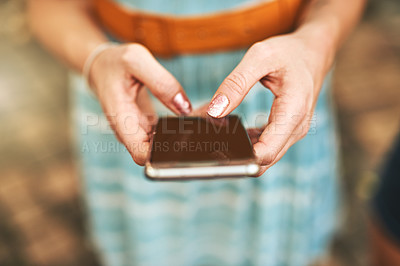 Buy stock photo Closeup of a unrecognizable woman browsing on her cellphone outside during the day