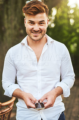 Buy stock photo Portrait of a cheerful young man browsing on his cellphone outside during the day