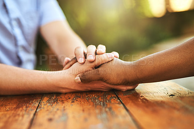Buy stock photo Shot of an unrecognizable person holding another person's hand in comfort outside during the day