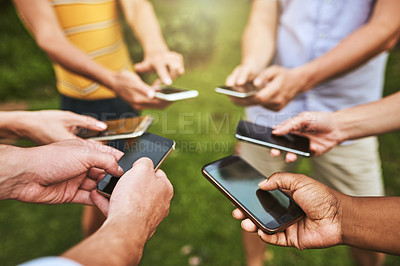 Buy stock photo Cropped shot of a group of unrecognizable people browsing on their cellphones outside during the day
