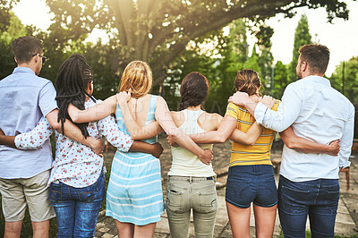 Buy stock photo Rearview shot of a group of young friends standing  arms around outside during the day