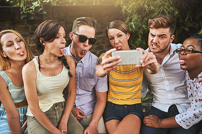 Buy stock photo Shot of a group of young friends taking a self portrait with a cellphone together outside during the day