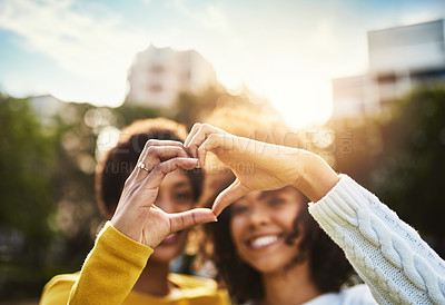 Buy stock photo Cropped shot of two friends forming a heart shape with their hands