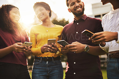 Buy stock photo Cropped shot of a group of friends using their cellphone while standing together