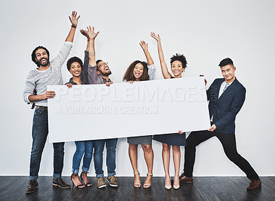 Buy stock photo Studio shot of a group of young businesspeople holding a blank sign and cheering against a gray background