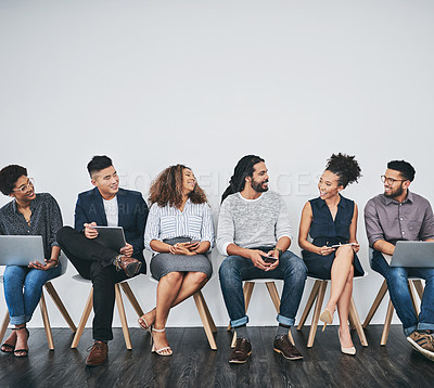 Buy stock photo Studio shot of a group of young businesspeople talking while waiting in line against a gray background