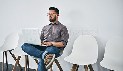Buy stock photo Studio shot of a young businessman using a laptop while waiting in line against a gray background