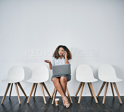 Buy stock photo Studio shot of a young businesswoman using a laptop and smartphone while waiting in line against a gray background